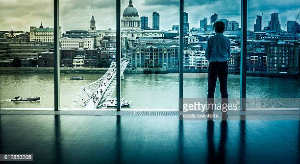 businessman looks at the london skyline from his office window - capitalism stock pictures, royalty-free photos & images