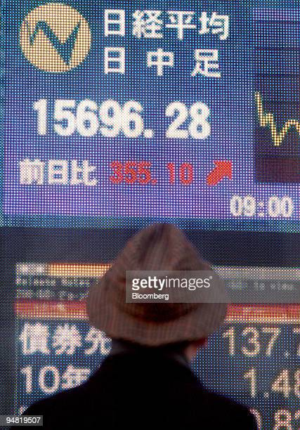 A businessman looks at the Nikkei 225 Index's closing value on a stock board in downtown Tokyo Thursday January 19 2006 Japan's Topix index staged...