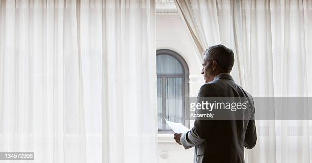 Businessman looks out a hotel window.