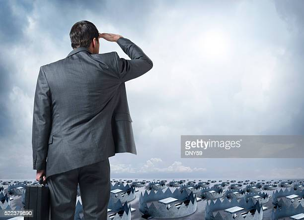 Businessman Looks Out Into The Distance Littered With Traps