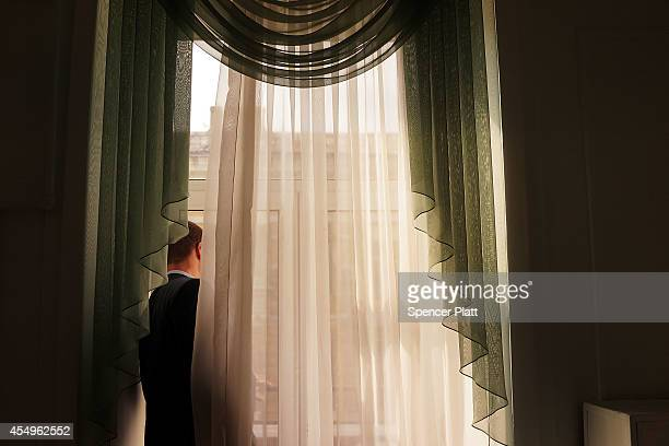 A businessman looks out of a window for the motorcade of Ukraine's president Petro Poroshenko in the embattled city of Mariupol in the country's east...