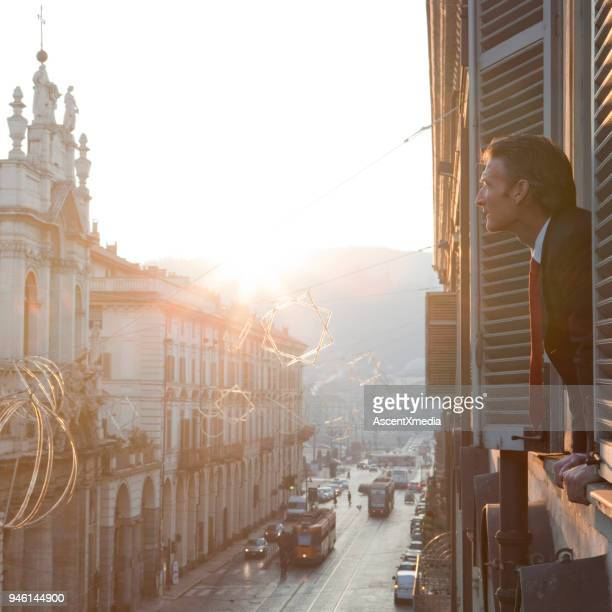 businessman looks out of window above city street. - turin stock pictures, royalty-free photos & images