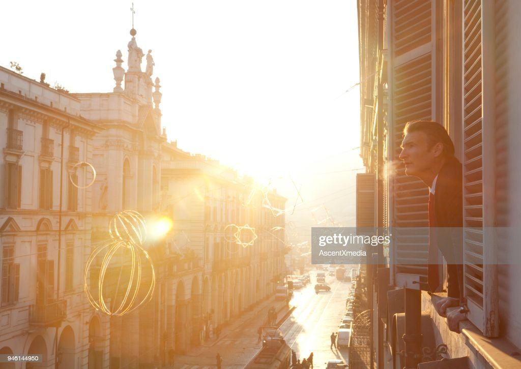 Businessman Looks Out Of Window Above City Street Stock Photo