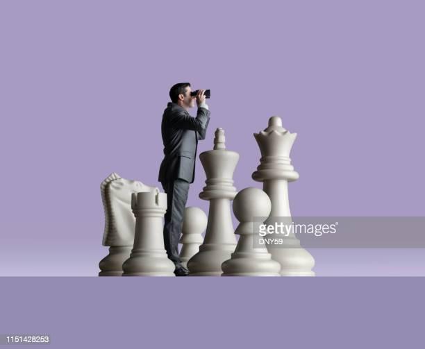 homme d'affaires regarde par des jumelles comme il se dresse parmi des pièces d'échecs - montrer la voie photos et images de collection