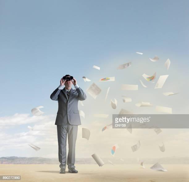 Businessman Looks Through Binoculars In Dust Storm