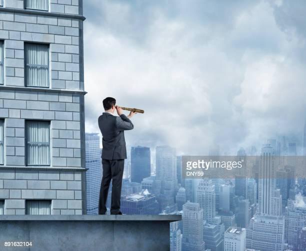 Businessman Looks Through Spyglass As Looks Toward A City Skyline