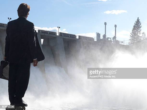 Businessman looks towards hydroelectric dam