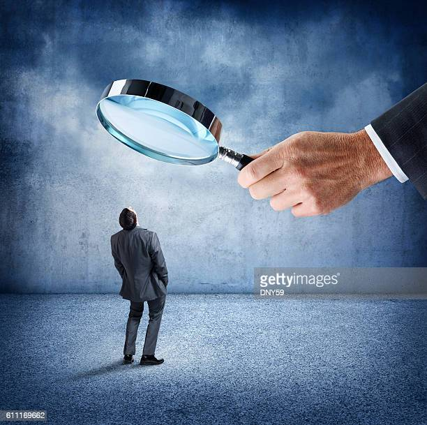 Businessman Looks Up At Businessman Holding Large Magnifying Glass