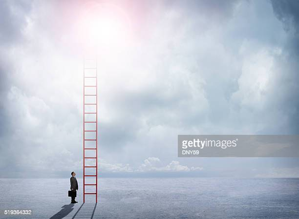 Businessman Looks Up At Red Ladder Extending Into The Clouds