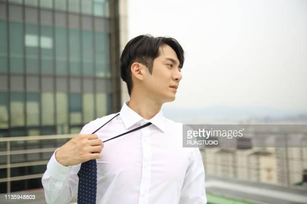 businessman loosening necktie outdoors - ネクタイ ストックフォトと画像