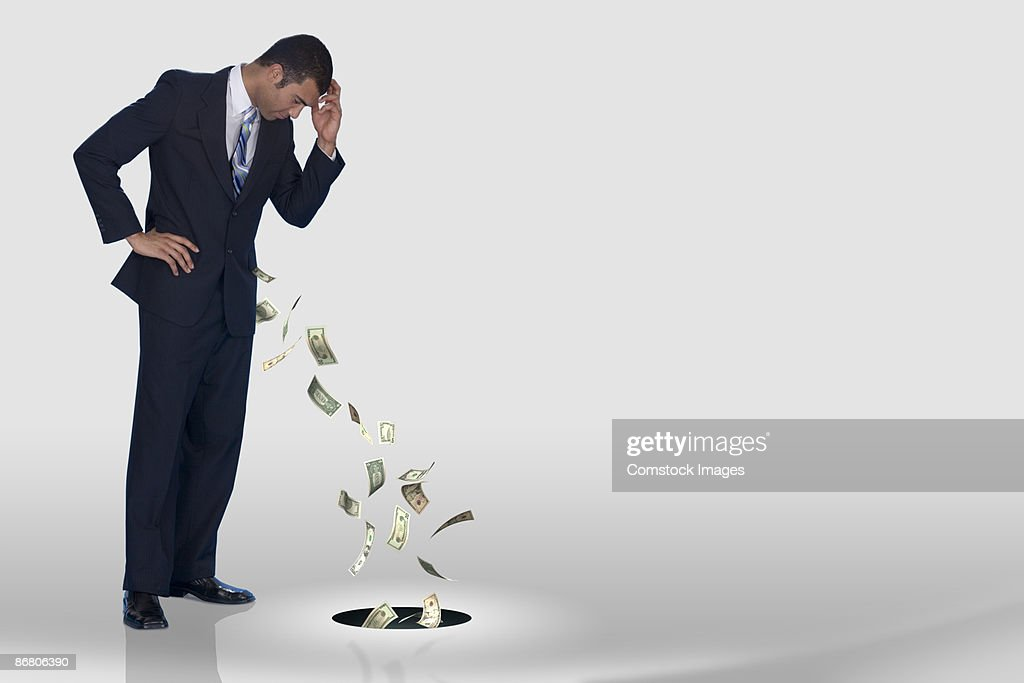 A businessman losing his money down the drain : Stock Photo