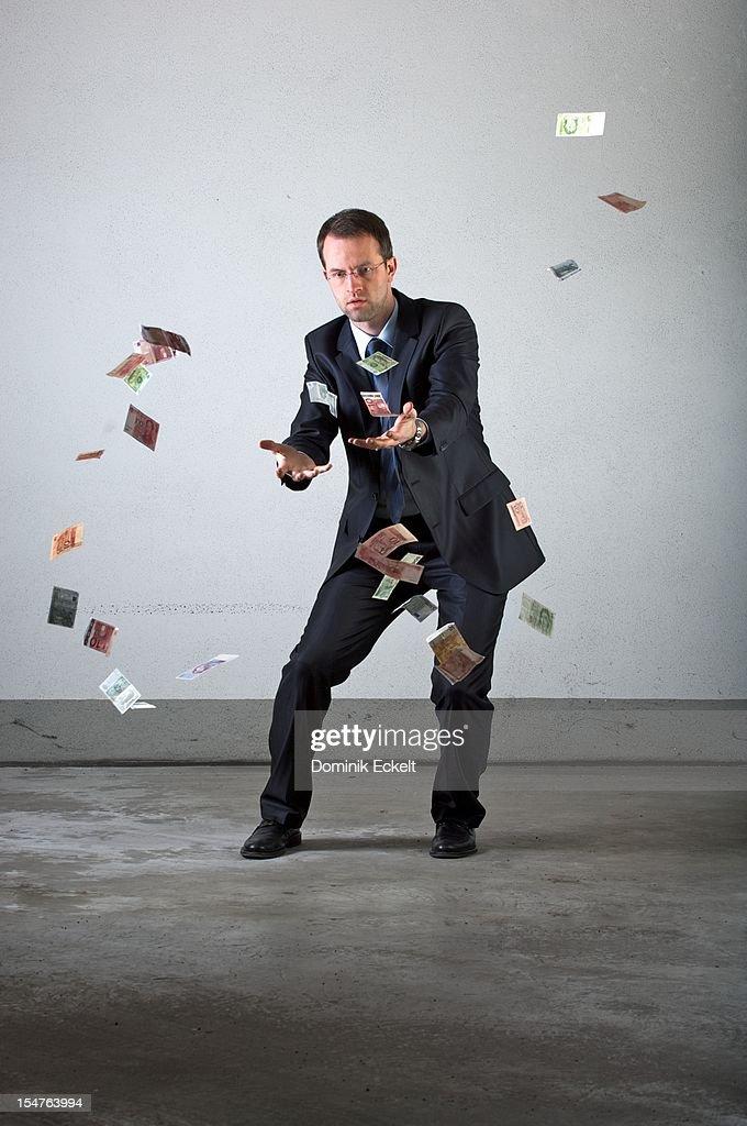 A businessman losing paper money : Stockfoto