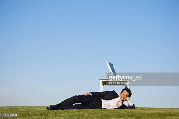 businessman lying by desk in field - lying on side stock pictures, royalty-free photos & images