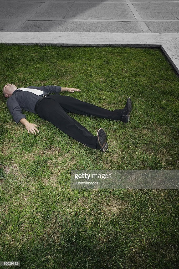 Businessman lying in grass : Stock Photo