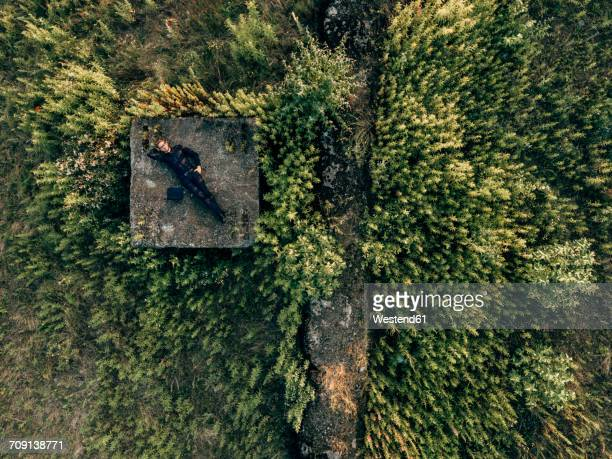 Businessman lying in the nature next to laptop