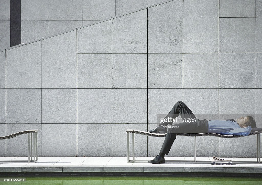Businessman lying on bench outdoors : Stockfoto
