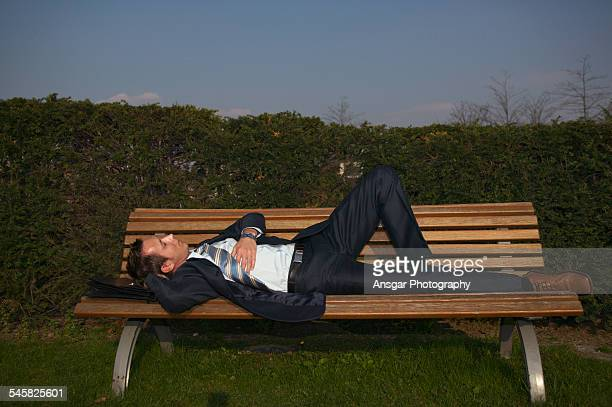 businessman lying on bench - lying down foto e immagini stock