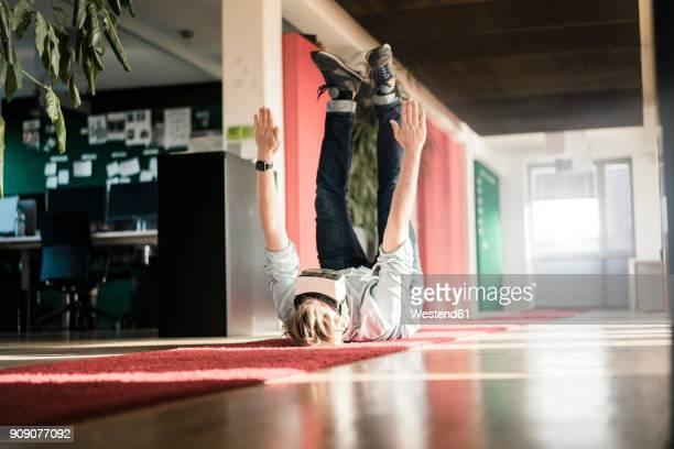 Businessman lying on carpet on the floor wearing VR glasses exercising