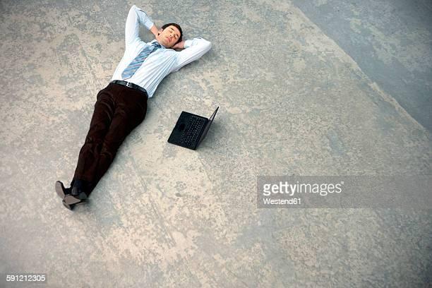 Businessman lying on floor next to laptop