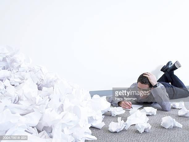 Businessman lying on floor, working beside pile of papers