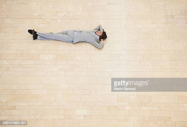 Businessman lying on foyer floor, elevated view