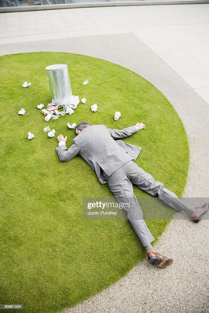 Businessman lying on grass by dustbin : Stock-Foto