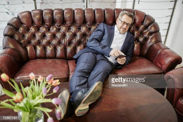 Businessman lying on leather couch using smartphone