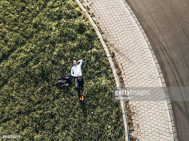 Businessman lying on traffic island in roundabout