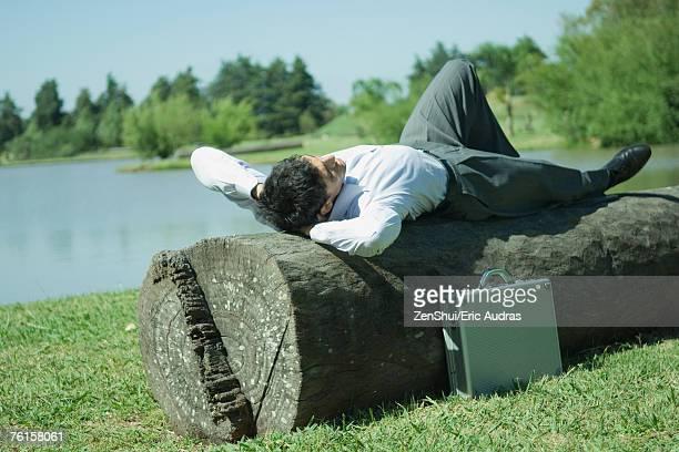 Businessman lying on tree trunk, hands behind head