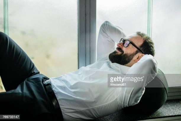 Businessman lying on window sill, taking a break