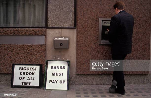 Businessman makes a cash withdrawal from an ATM at a time when the pension fund of Mirror Group Newspapers by its tycoon owner, Robert Maxwell was...