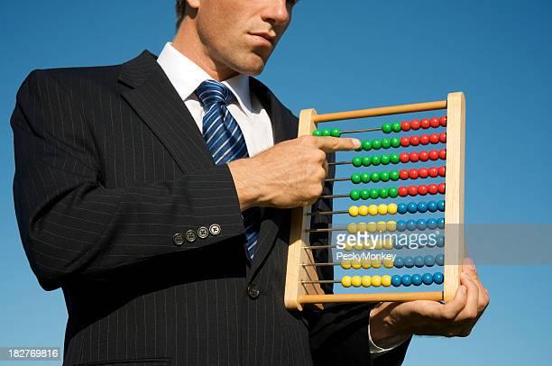 Geschäftsmann macht Berechnungen auf bunten Abacus