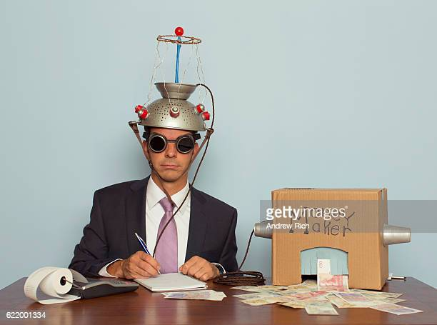 businessman makes money with helmet and money machine - vintage stock stock pictures, royalty-free photos & images