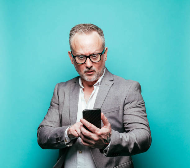 Businessman making a face using smartphone