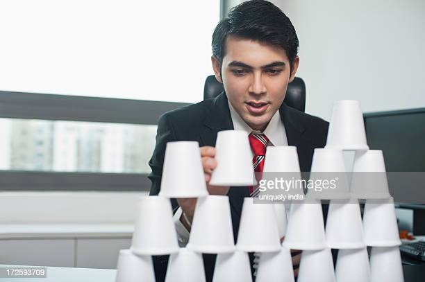 Businessman making a pyramid with disposable cups