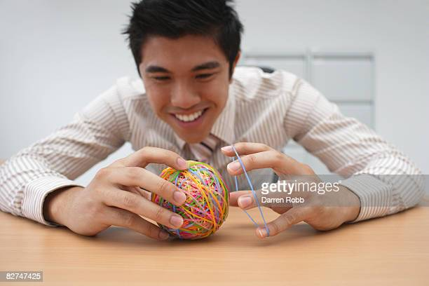 businessman making an elastic band ball at desk - wasting time stock pictures, royalty-free photos & images