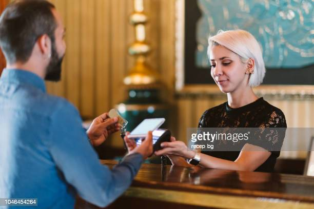 businessman making contactless payment at hotel reception - hotel stock pictures, royalty-free photos & images