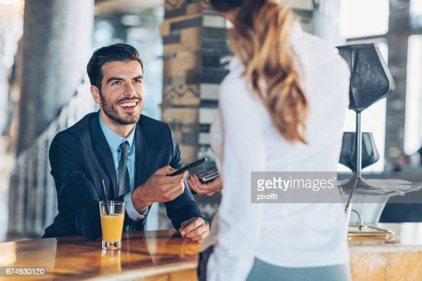 Businessman making contactless payment in a hotel's bar