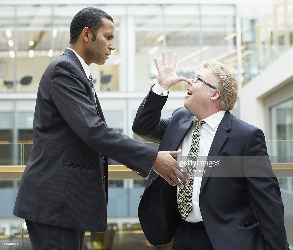 Businessman making face at co-worker : Stock Photo