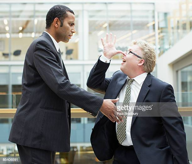 businessman making face at co-worker - opstand stockfoto's en -beelden