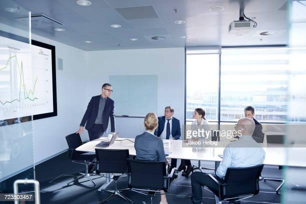 Businessman making flat screen presentation to team in boardroom