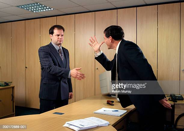 businessman making hand gesture across desk to male colleague - middle finger funny stock photos and pictures
