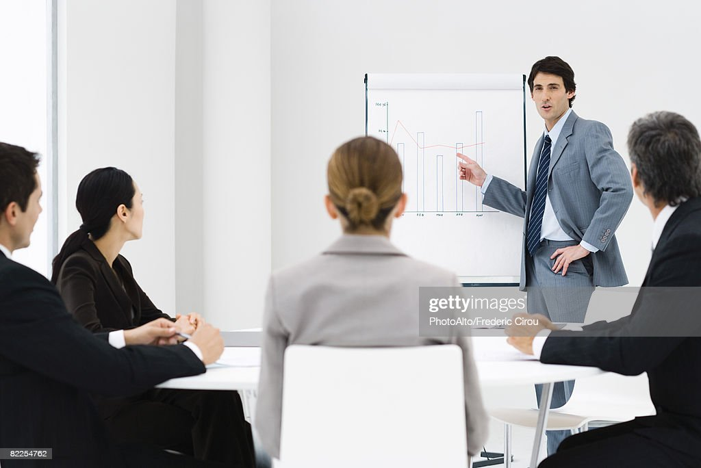 Businessman making presentation, colleagues watching : Stock Photo