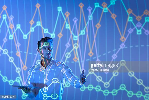 Businessman making presentation with graphical projected images