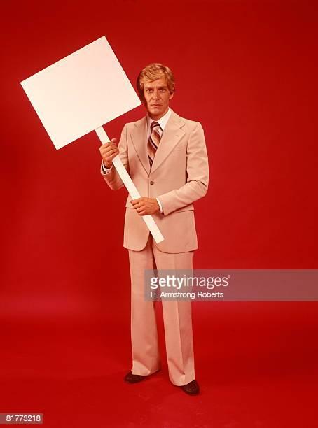 businessman man suit holding blank sign placard red background retro. - 1970年 ストックフォトと画像