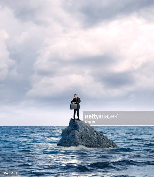 businessman marooned on rock in ocean checks his watch - stranded stock photos and pictures
