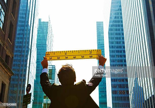 Businessman measuring city buildings with tape.
