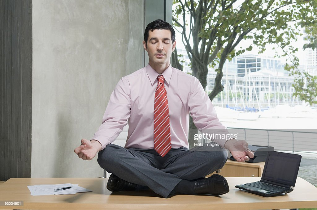 Businessman Meditating In An Office