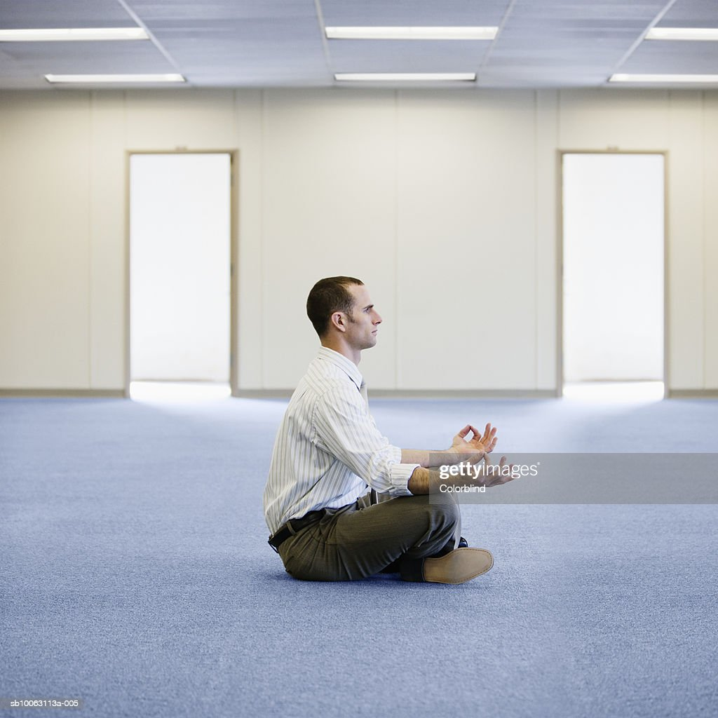 Businessman Meditating In Empty Office, Side View