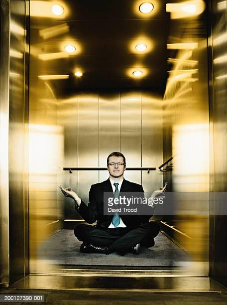 Businessman meditating in lift (Digital Enhancement)